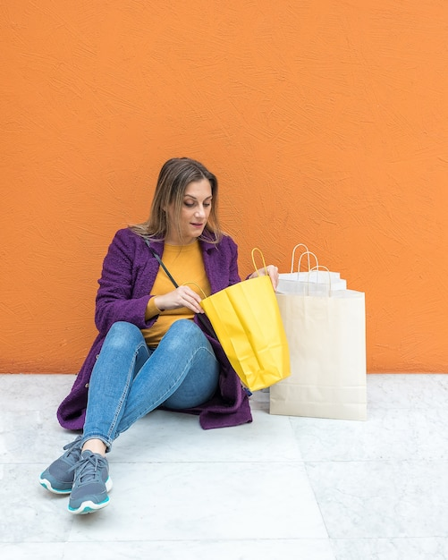 Femme Assise Sur Le Sol à La Recherche De Sacs à Provisions Photo Premium