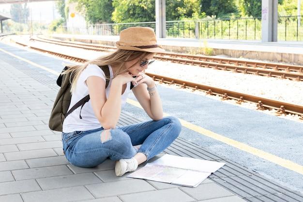 Femme Assise Sur Un Sol Et Regardant Une Carte Photo gratuit