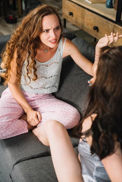 Femme Assise Avec Son Amie En Haussant Les épaules Photo gratuit