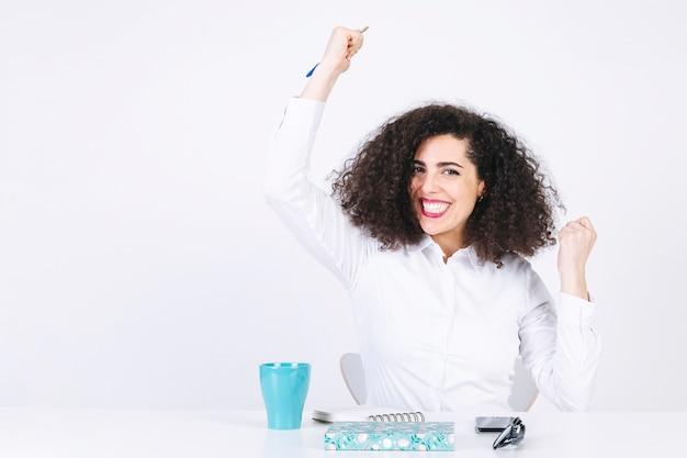 Femme assise à table et célébrant le succès Photo gratuit