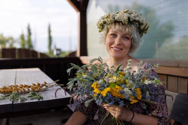 Femme assise et tenant un bouquet de fleurs sauvages Photo Premium