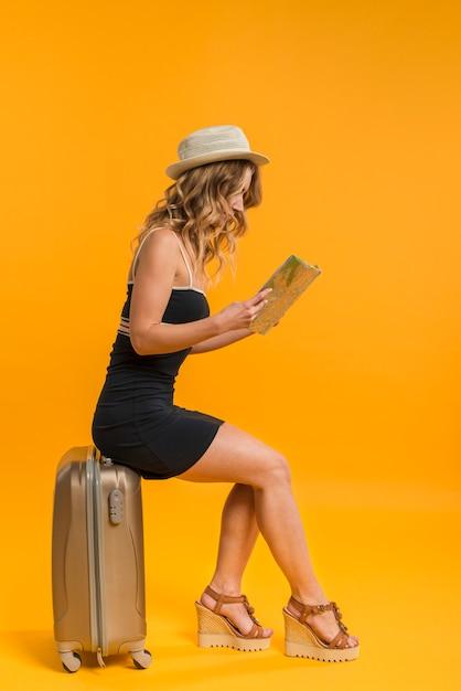 Femme Assise Sur Une Valise Et Explorant La Carte Photo gratuit