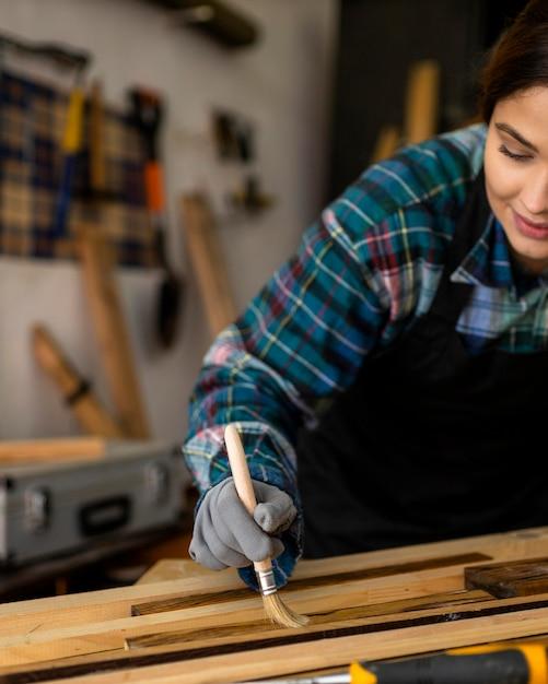 Femme En Atelier De Brossage De La Poussière De Planches De Bois Photo gratuit