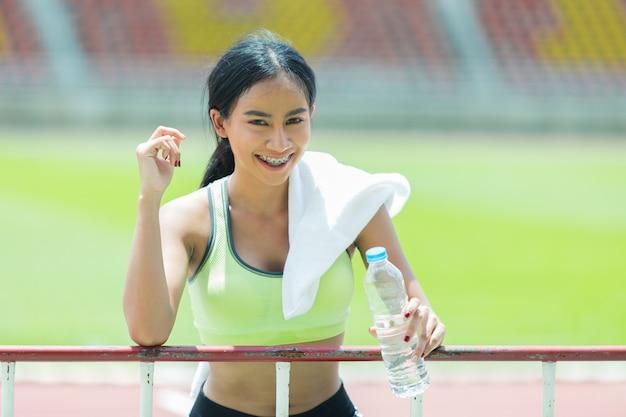 Femme athlète prend une pause et boit de l'eau Photo gratuit