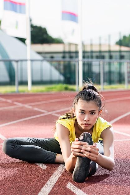 Femme athlète qui s'étend sur piste avant de courir Photo Premium