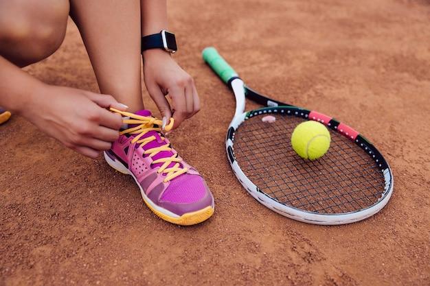 Femme Athlète Se Prépare Pour Jouer Au Tennis, Attacher Les Lacets. Photo gratuit