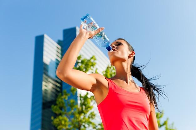 Femme athlétique buvant de l'eau en milieu urbain Photo Premium