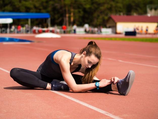 Femme Athlétique étirant Ses Muscles Avant De Faire Du Jogging Sur La Bonne Voie Photo Premium