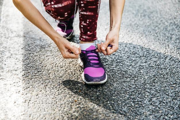 Femme attachant des chaussures de course sur route Photo gratuit
