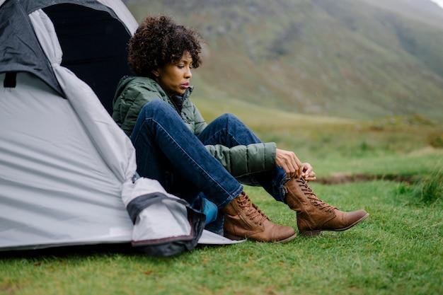 Femme attachant ses lacets près de sa tente Photo gratuit
