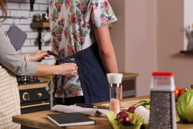 Femme, attacher, tablier, homme, cuisine Photo gratuit