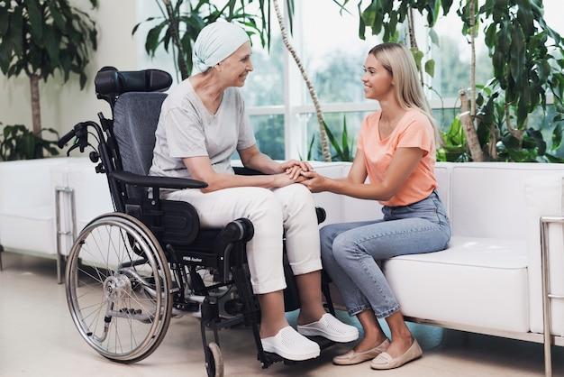 Une femme atteinte de cancer est assise dans un fauteuil roulant Photo Premium