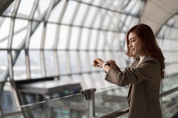 Femme, Attente, Vol, Regarder, Montre Intelligente, Aéroport Photo Premium