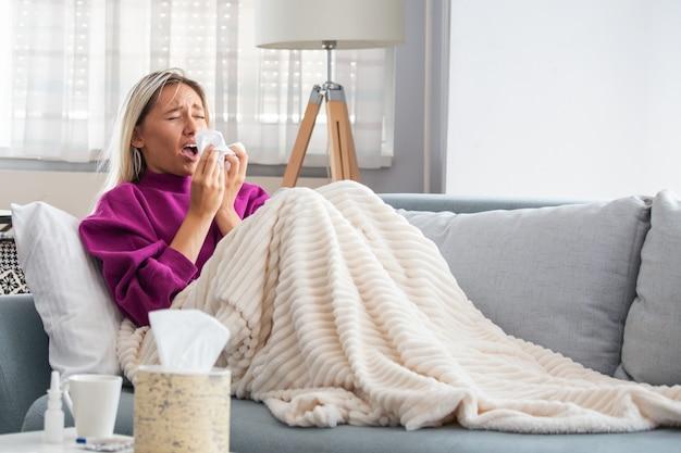 Femme attrapée rhume et grippe en éternuant dans les tissus. Photo Premium