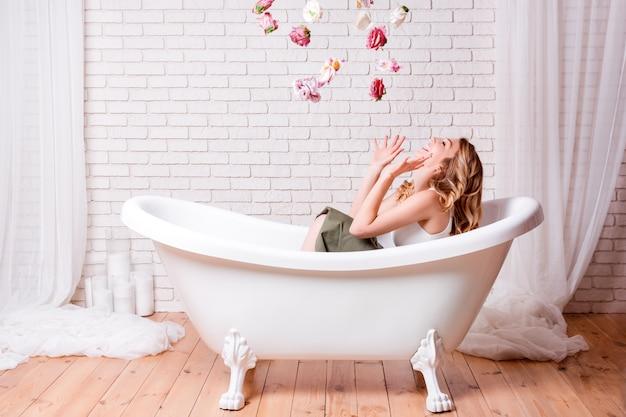 Femme au bain s'amuser avec des fleurs. belle jeune femme blonde, appréciant le bain agréable, levant et souriant Photo Premium