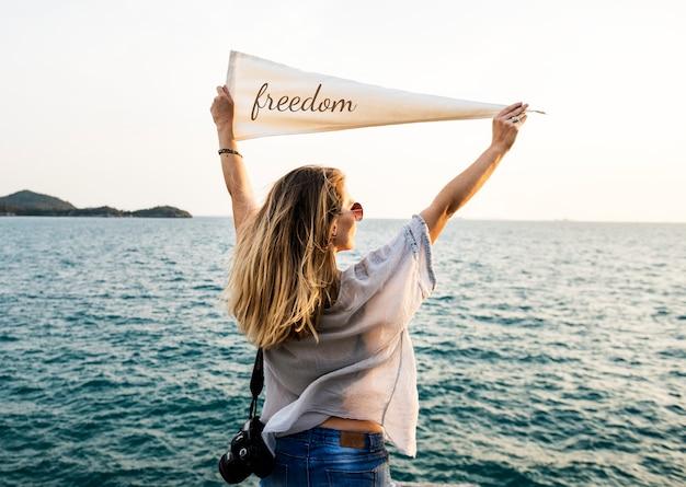 Femme Au Bord De La Mer Tenant Un Drapeau Avec Inscription Liberté Photo gratuit