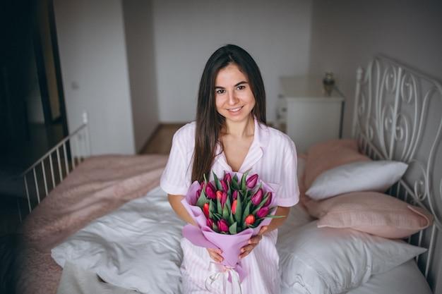 Femme au bouquet de fleurs dans la chambre Photo gratuit
