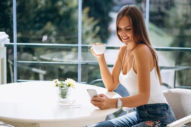 Femme au café prenant un café et parlant au téléphone Photo gratuit