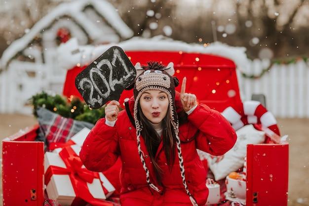 Femme Au Chapeau Comme Un Taureau Posant Avec Plaque Signalétique 2021 En Rouge Ouvert. Neige Photo Premium