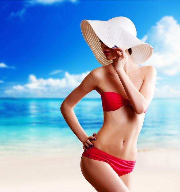 Femme au chapeau sur la plage Photo Premium
