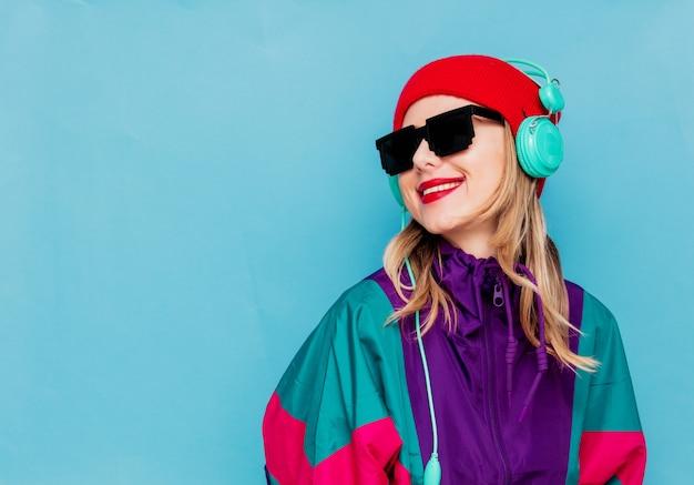 Femme au chapeau rouge, lunettes de soleil et costume des années 90 avec un casque Photo Premium