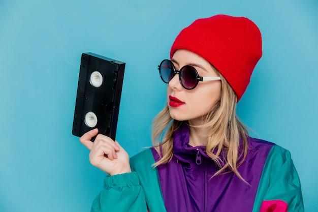 Femme au chapeau rouge, lunettes de soleil et costume des années 90 avec cassette vhs Photo Premium