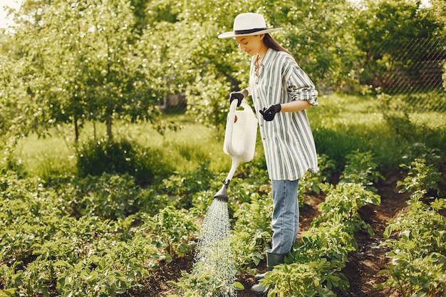 Femme Au Chapeau Tenant L'entonnoir Et Travaille Dans Un Jardin Photo gratuit