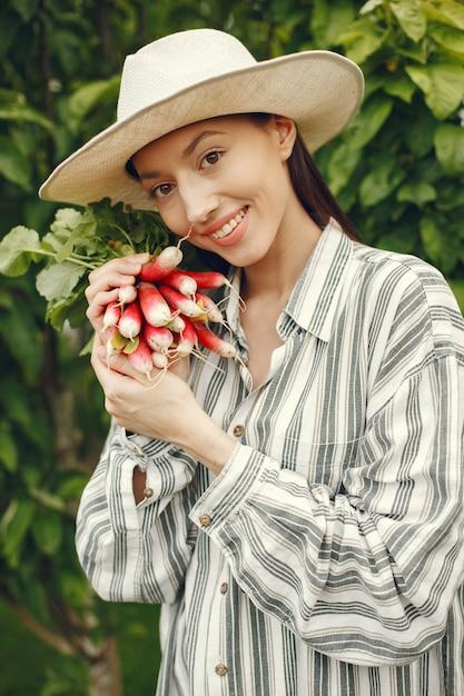 Femme Au Chapeau Tenant Des Radis Frais Photo gratuit