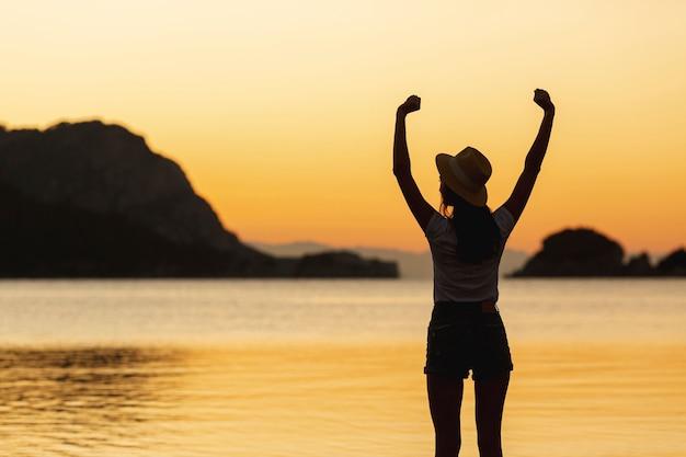 Femme au coucher du soleil au bord d'un lac Photo gratuit