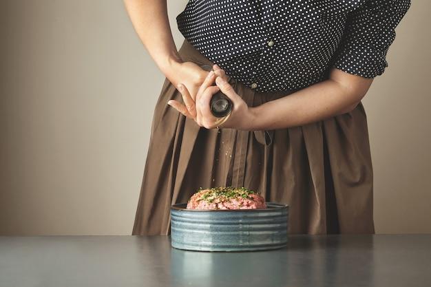 Femme Au Foyer Ajoute Un Peu D'épices Poivrées Dans La Viande Hachée Dans Un Bol En Céramique Sur Table Bleue Photo gratuit