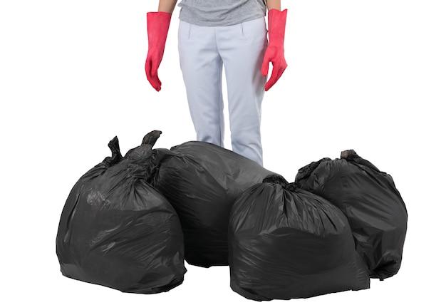 Femme au foyer debout parmi les sacs à ordures isolé sur blanc Photo Premium