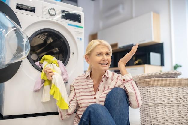 Femme Au Foyer. Femme Au Foyer Blonde En Chemise Rayée Assis Près De La Machine à Laver Photo Premium