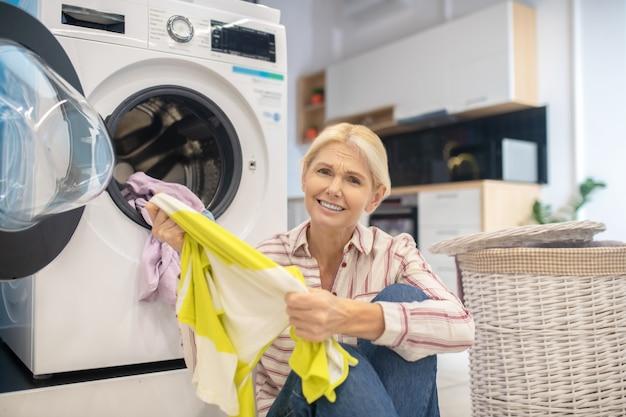 Femme Au Foyer. Femme Au Foyer Blonde En Chemise Rayée Et Jeans Assis Près De La Machine à Laver Photo Premium