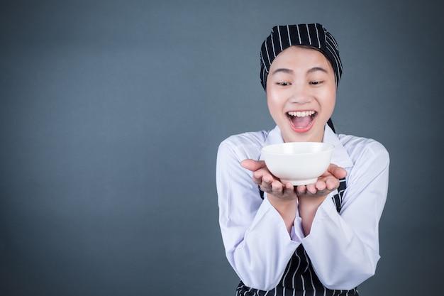 Une femme au foyer tenant une assiette vide avec de la nourriture Photo gratuit