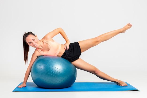 Femme au gymnase sur tapis avec entraînement de balle bondissante Photo gratuit