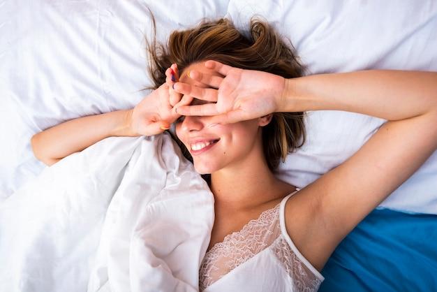 Femme au lit couvrant ses yeux Photo gratuit