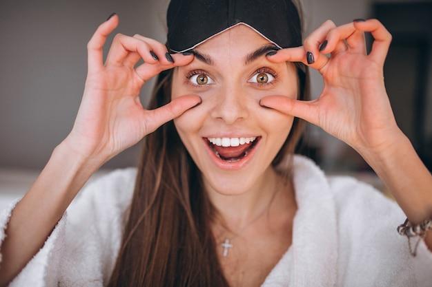 Femme au lit avec masque de sommeil Photo gratuit