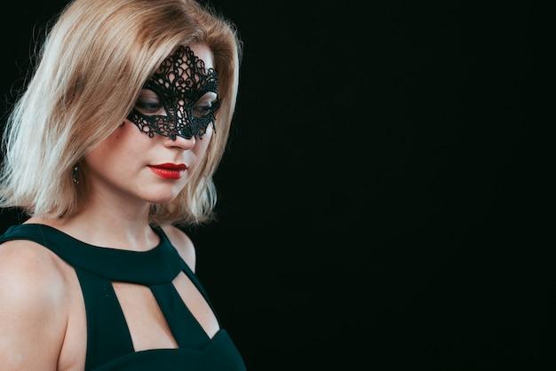 Femme au masque de carnaval noir, regardant vers le bas Photo gratuit
