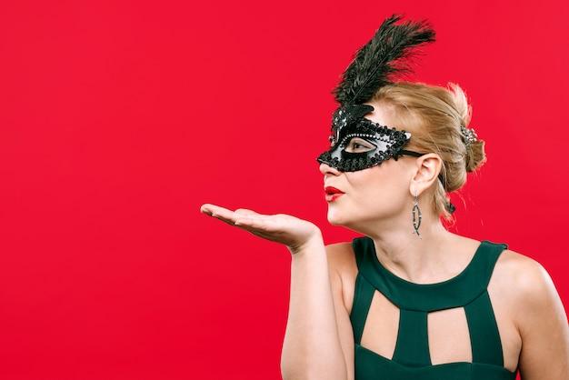 Femme au masque noir souffle bisou Photo gratuit