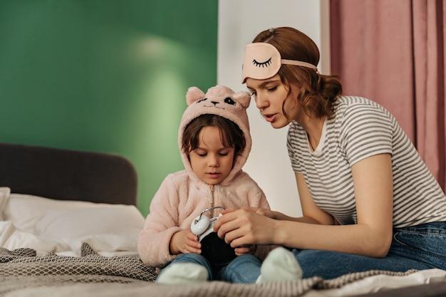 Femme Au Masque De Sommeil Apprend à Sa Fille En Pyjama Mignon Comment Démarrer Le Réveil. Photo gratuit