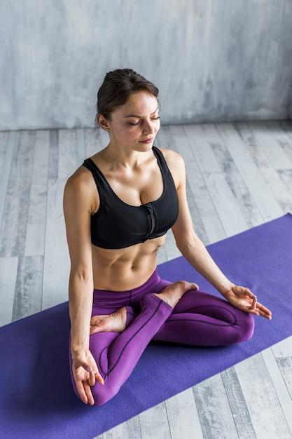 Femme au repos dans une posture de yoga au lotus Photo gratuit