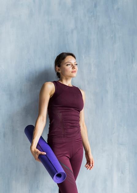 Femme au repos près du mur tout en tenant un tapis de yoga Photo gratuit