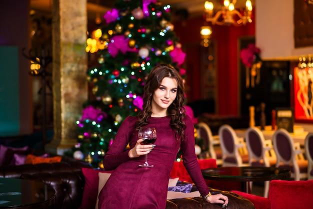 La femme au restaurant avec un verre de champagne pour le nouvel an. Photo Premium
