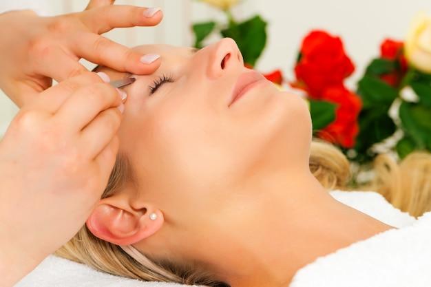 Femme au salon de beauté obtient les sourcils coupés Photo Premium
