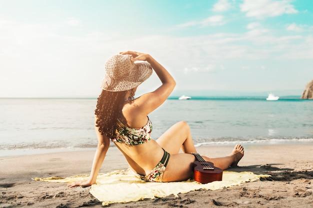 Femme au soleil sur la plage de sable fin Photo gratuit
