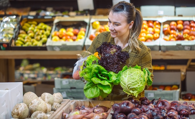 Femme Au Supermarché. Belle Jeune Femme, Faire Du Shopping Dans Un Supermarché Et Acheter Des Légumes Biologiques Frais Photo gratuit