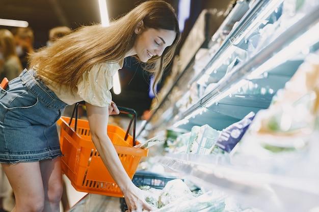 Femme Au Supermarché. Femme Dans Un T-shirt Marron. Les Gens Choisissent Les Produits. Photo gratuit