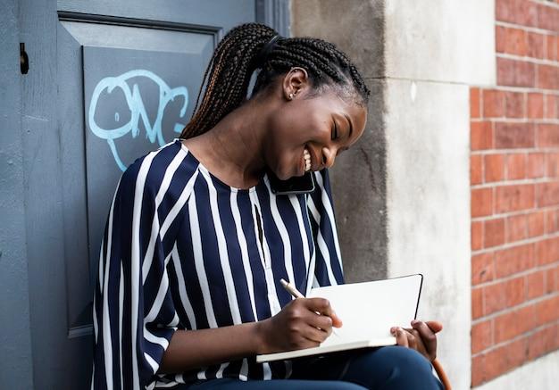 Femme au téléphone tout en prenant des notes Photo Premium
