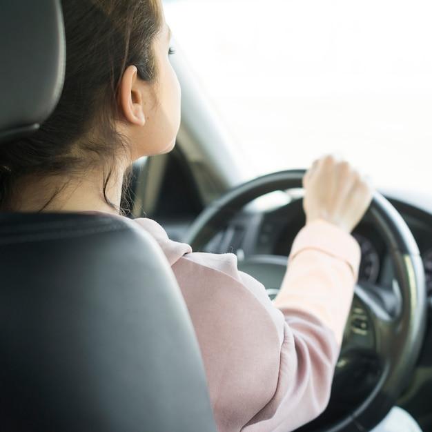 Femme Au Volant Sur La Vue De L'épaule Photo gratuit