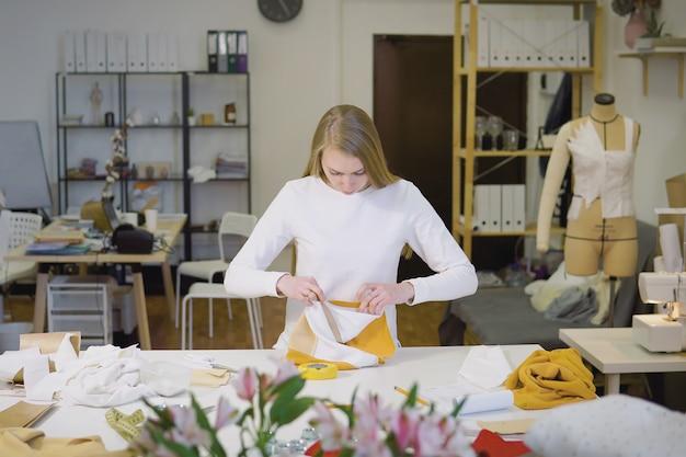 Femme aux cheveux blonds, pigiste ou designer de mode ou tailleur travaillant sur un dessin ou un modèle avec des tissus colorés en atelier Photo Premium